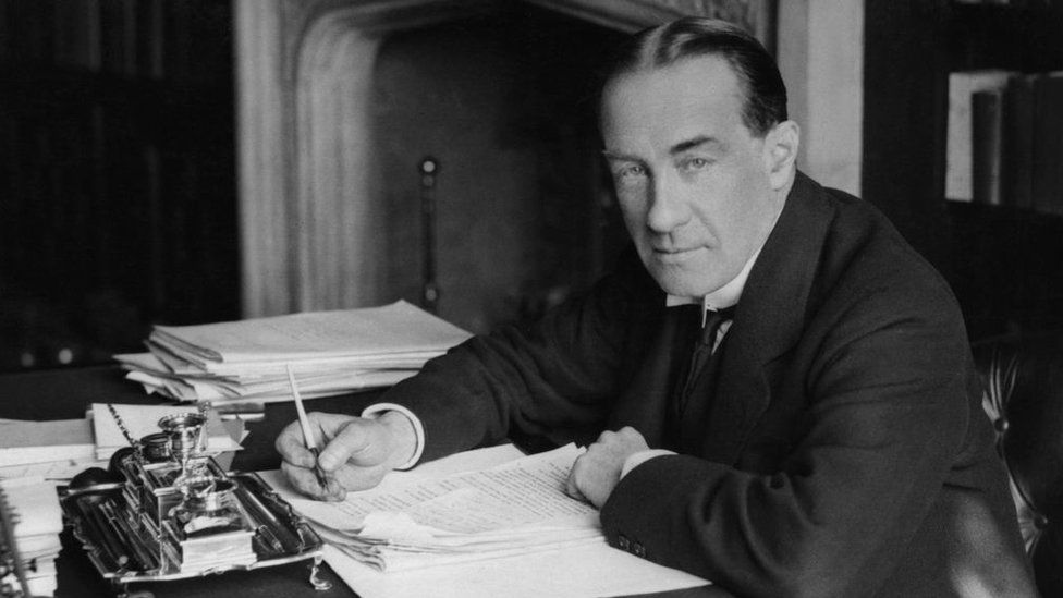Stanley Baldwin sitting at a desk