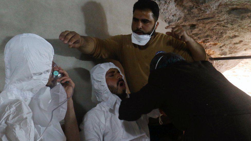 A man breathes through an oxygen mask in Khan Sheikhoun