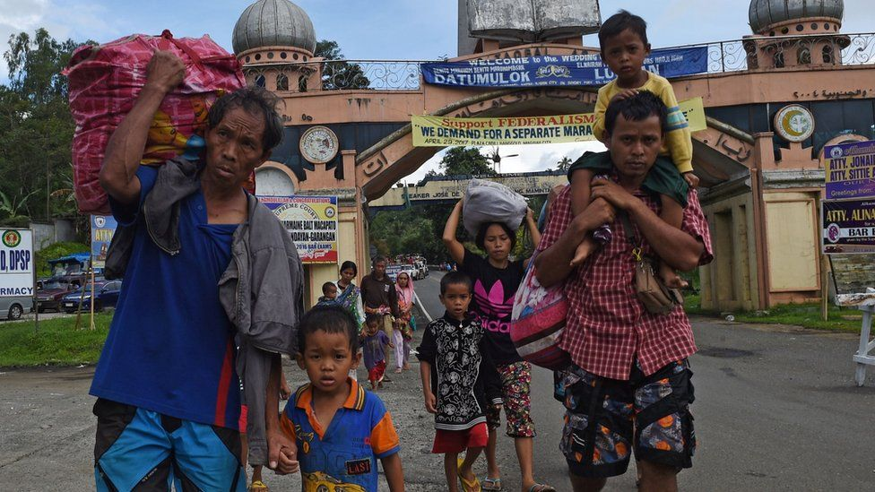A family carrying their belongings flee from Marawi on the southern island of Mindanao