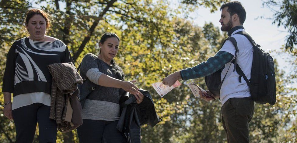 Two women walk past a man in a sunny street handing out flyers - one accepts the offer as she walks past