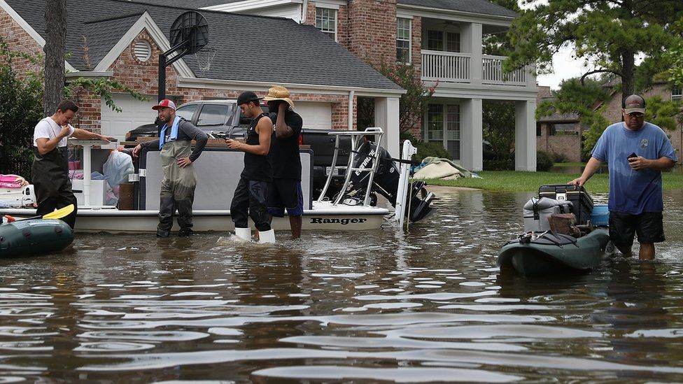 People use boats to help bring items out of homes on September 3, 2017 in Houston, Texas.
