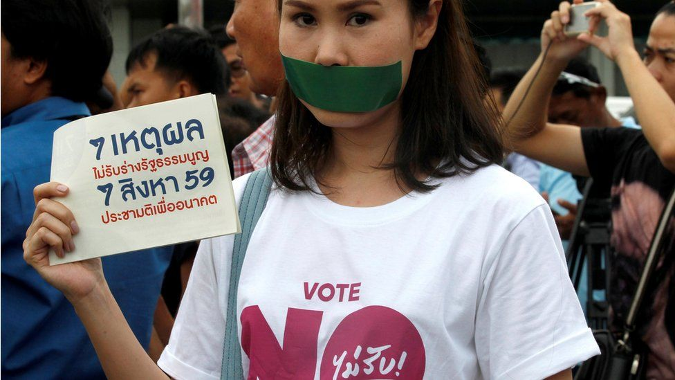 """An activist holds a placard reading """"7 Reasons To Not Accept Constitution"""""""