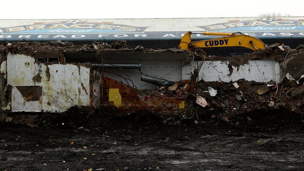 A yellow bulldozer stands out among the debris of Ninian Park football stadium's demolition