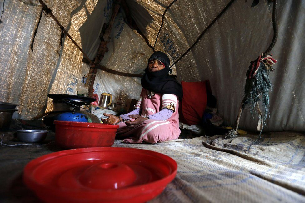 A woman sits on the floor of a makeshift house
