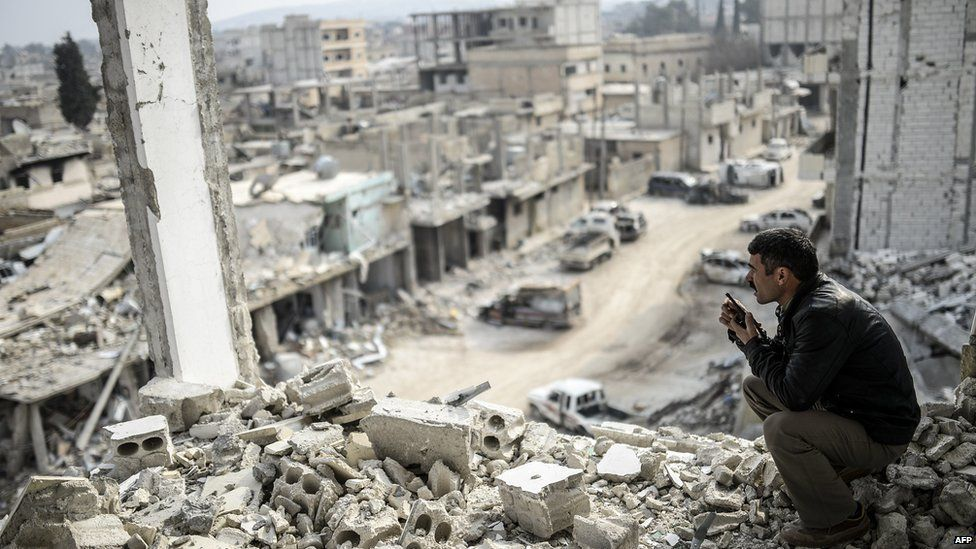 A Kurdish man talks with a radio as he checks the eastern part of the Syrian border town of Kobane, known as Ain al-Arab, on 28 January 2015