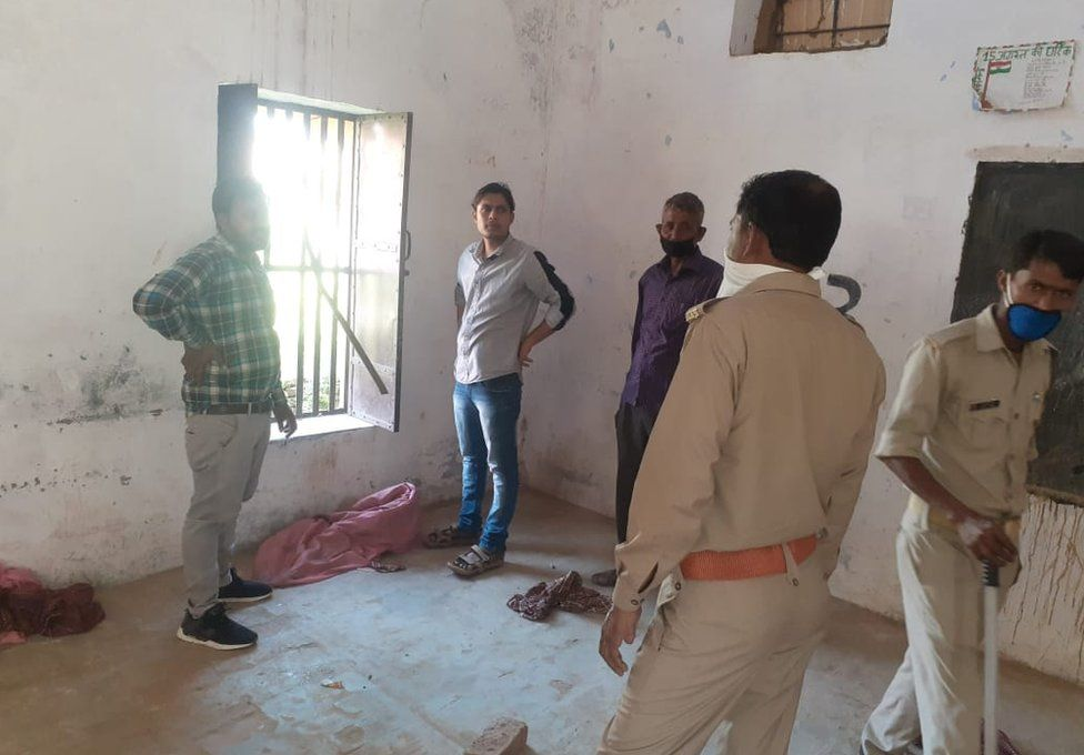 Police inspect the broken window at a quarantine centre in Bulandshahar district in Uttar Pradesh from where 16 people escaped
