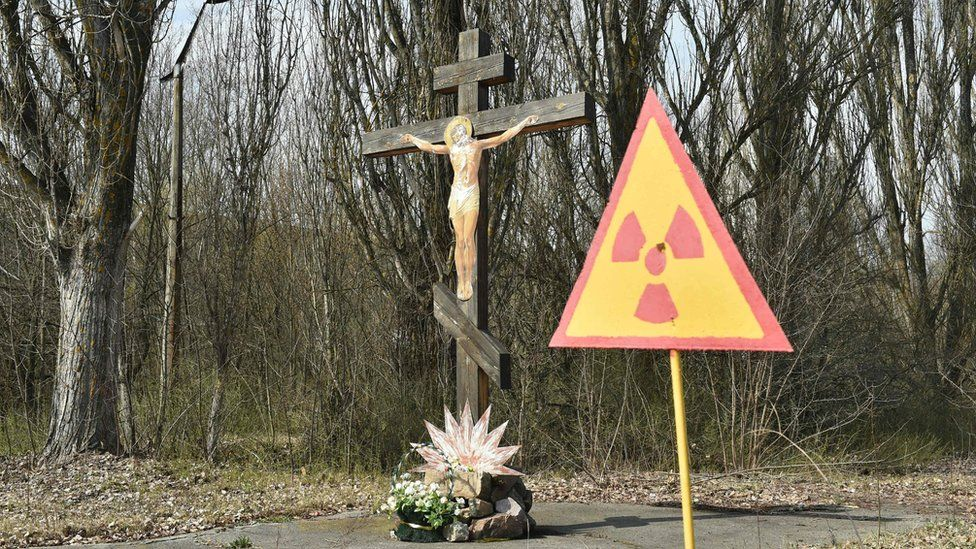 A sign of radioactivity set in front of crucifix in ghost city of Pripyat near Chernobyl
