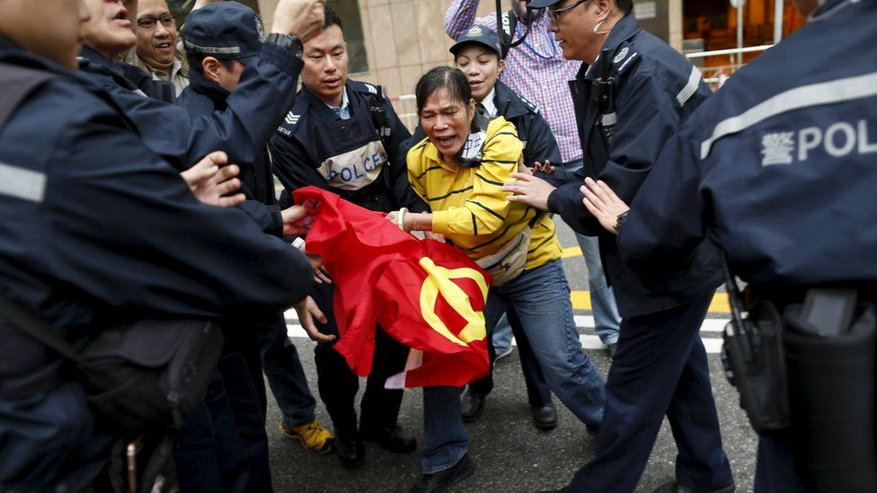 A woman protesting the disappearance of Hong Kong booksellers clutches a Chinese flag