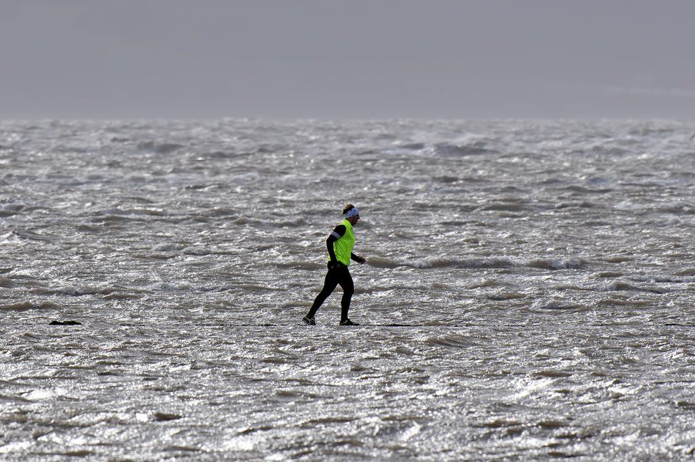 A jogger running by water