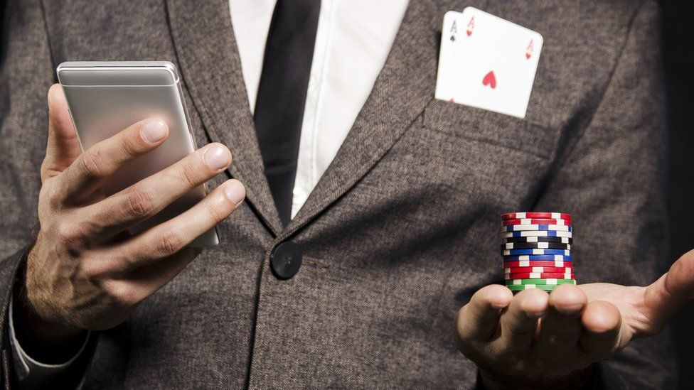 A man in a suit holding poker chips and a smartphone