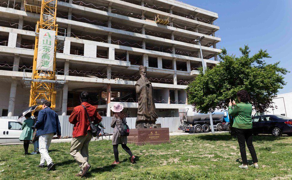 Kineski turisti prolaze pored statue Konfučija ispred mesta gde je nekada bila ambasada