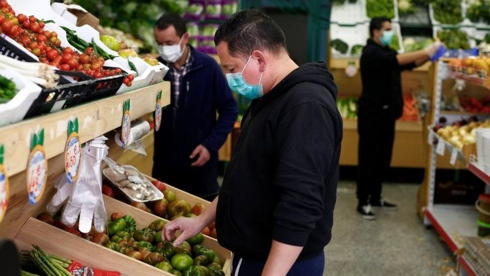 People wearing masks choose vegetables in a supermarket in Madrid, Spain. Photo: 14 March 2020