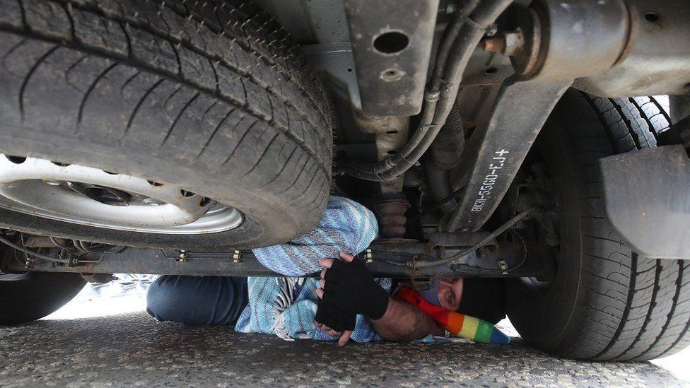 Man under immigration van