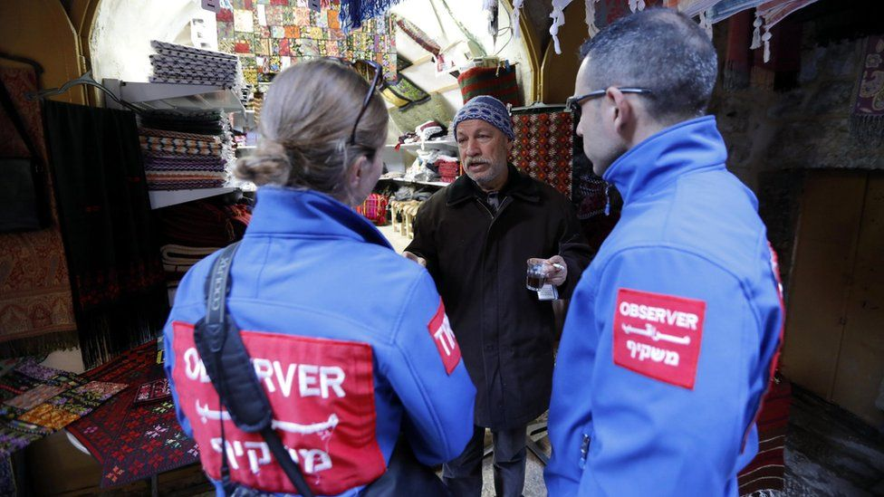 Members of the Temporary International Presence in Hebron (TIPH) speak with a Palestinian trader in the old city of Hebron (29 January 2019)