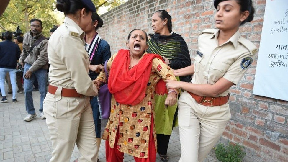 Gujarat Police officials detain a demonstrator during a protest against the Indian government's Citizenship Amendment Bill outside Indian Institute of Management (IIM) in Ahmedabad on Monday