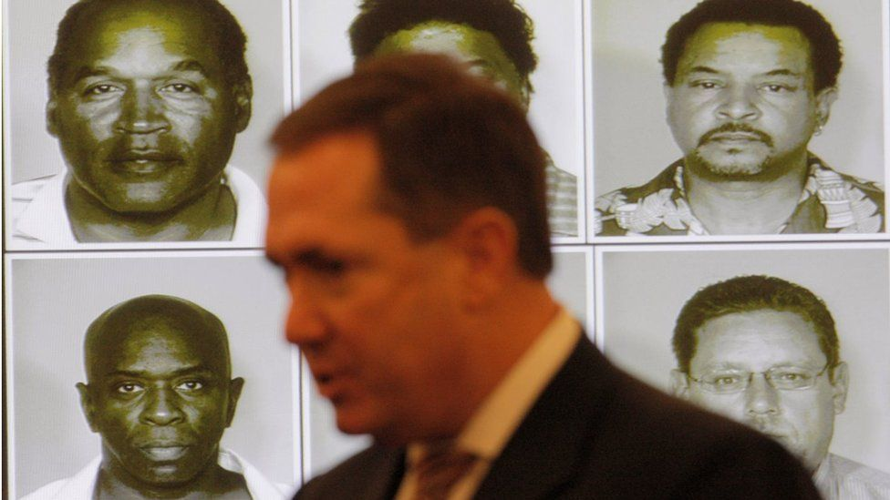 Mug shots of the alleged co-defendants are projected on the wall as Clark County District Attorney David Roger speaks as OJ Simpson appears in court at the start of closing arguments for his trial at the Clark County Regional Justice Center on October 2, 2008 in Las Vegas, Nevada