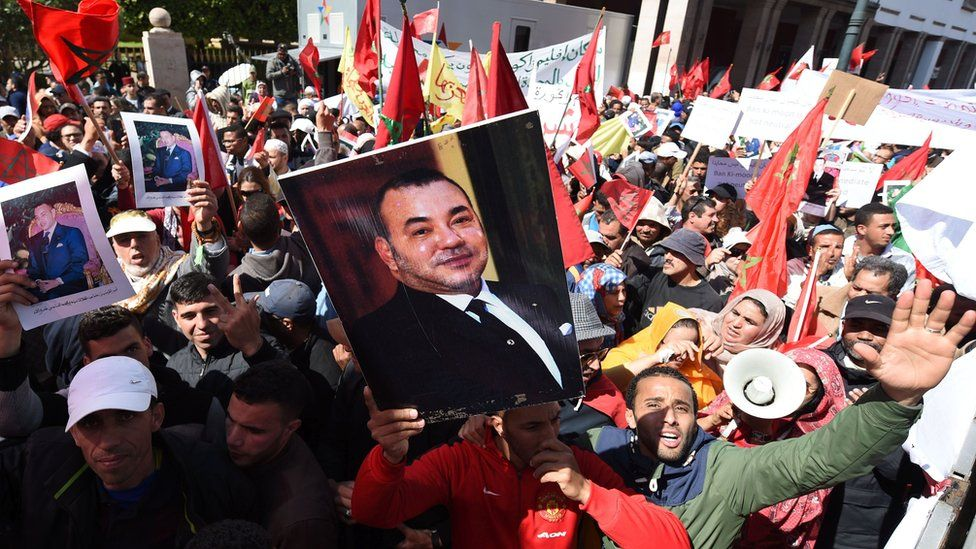 moroccan protesters lift up photos of the king