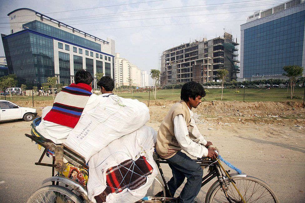 In this picture taken 06 December 2006, an Indian man pulls a cycle rickshaw past office buildings, in Gurgaon, some 30 km south of New Delhi. India's estimated 300-million-strong middle-class is not only gaining from the country's rapidly growing economy but is also driving the consumption boom. India's economy -- the second-fastest growing after China's -- grew 9.2 percent in the second quarter to September.