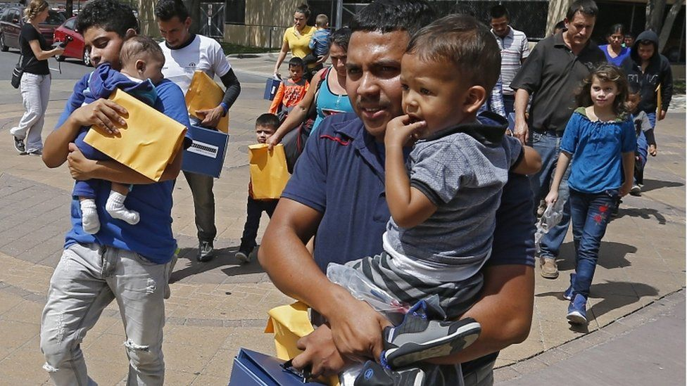 Migrant families carrying young children