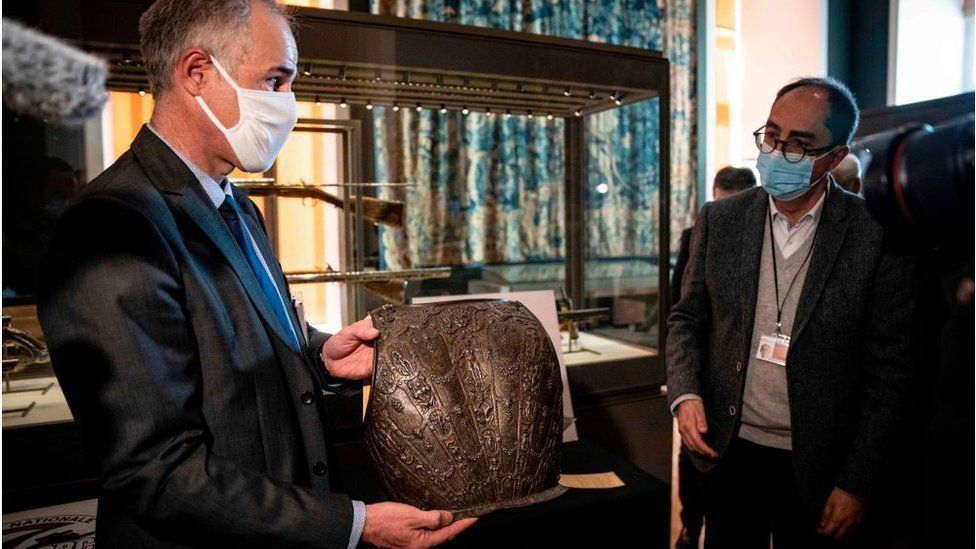 Two men looking at the chest plate of armour