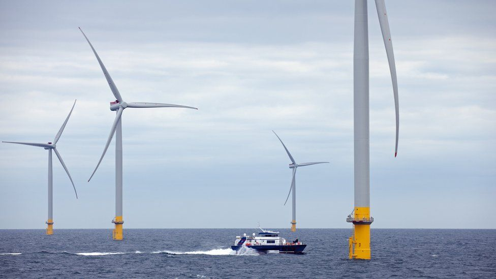 Boat approaches wind turbine at sea