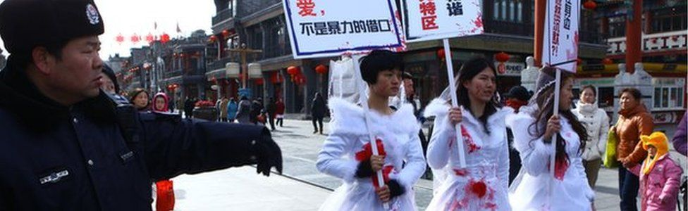 Li Tingting in the middle and two others wear paint-spattered wedding dresses