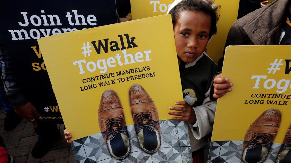 A child holds a placard during a walk to commemorate what would have been Nelson Mandela's 99th birthday in Cape Town, South Africa, July 18, 2011
