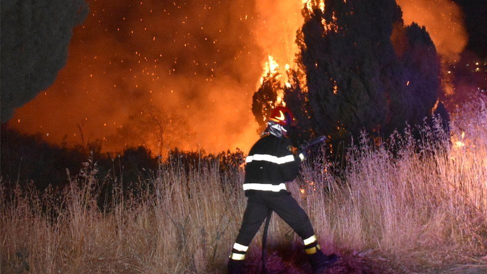 A firefighter battles the flames after a wildfire broke out in Petralia Soprana, Italy, 10 August 2021