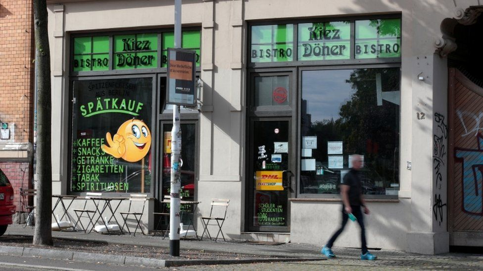 A man walks in front of a kebab shop where a person was killed in 2019 in Halle, Germany, July 28, 2020.