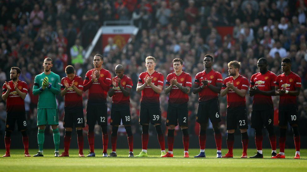 Manchester United players taking part in a minute's applause for Eric Harrison