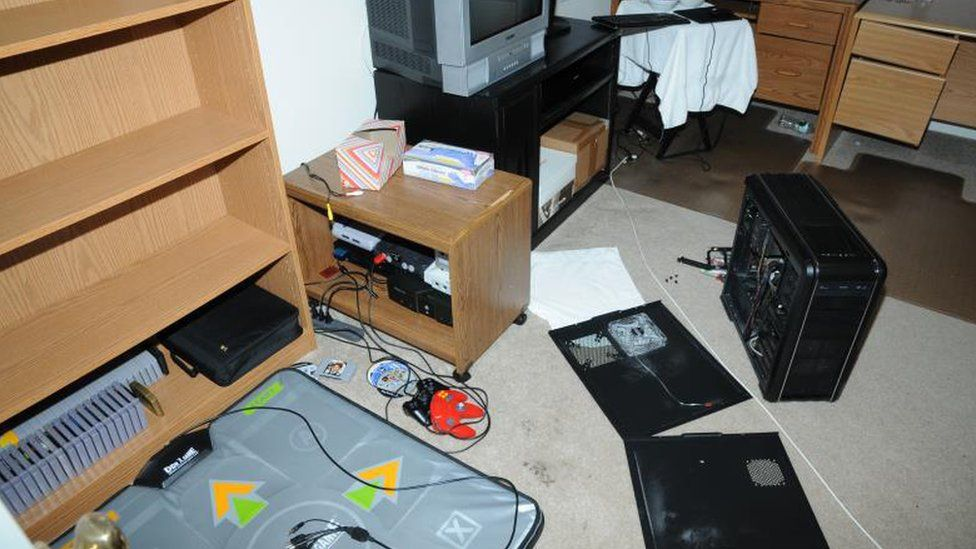 A dance mat and electronic equipment strewn across a bedroom floor