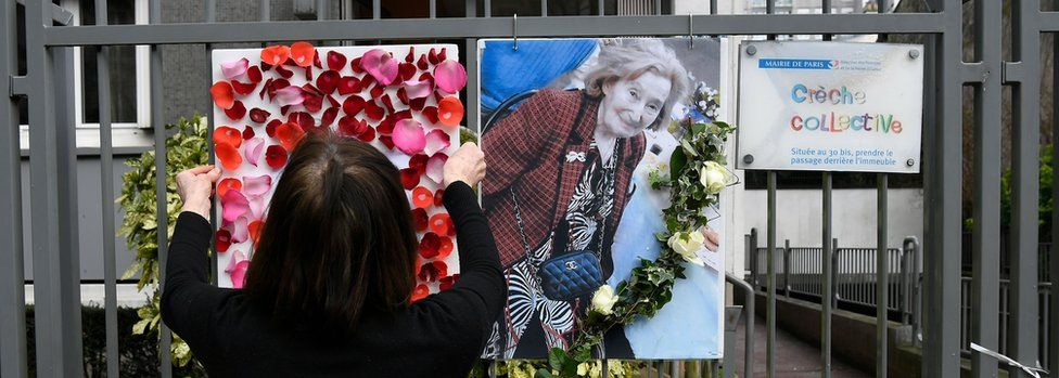 A woman places a picture and tributes to Mireille Knoll on the fence surrounding her building in Paris on March 27