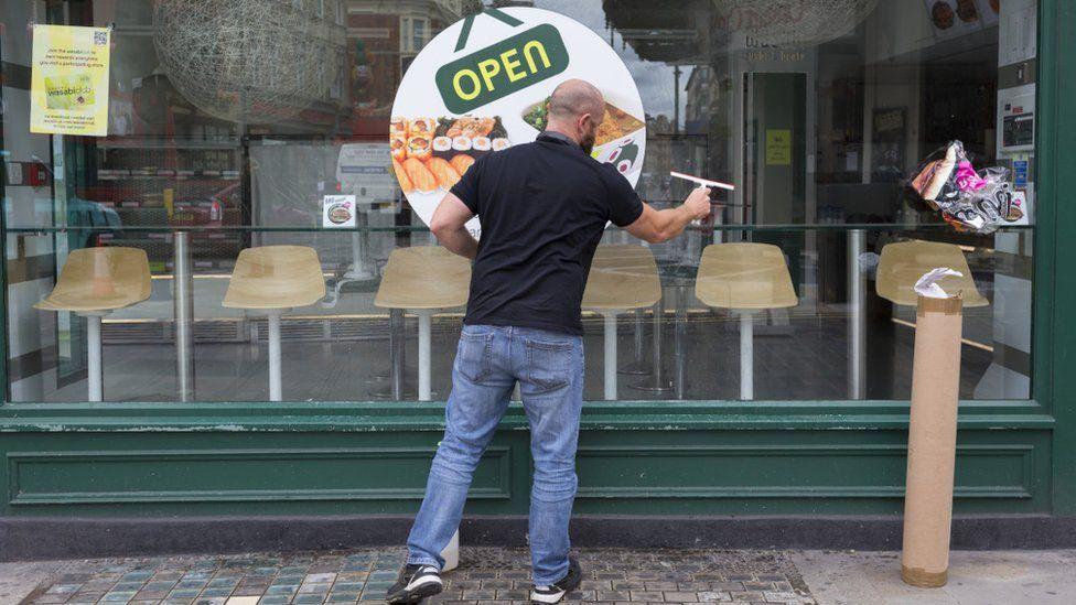 Man cleans restaurant window