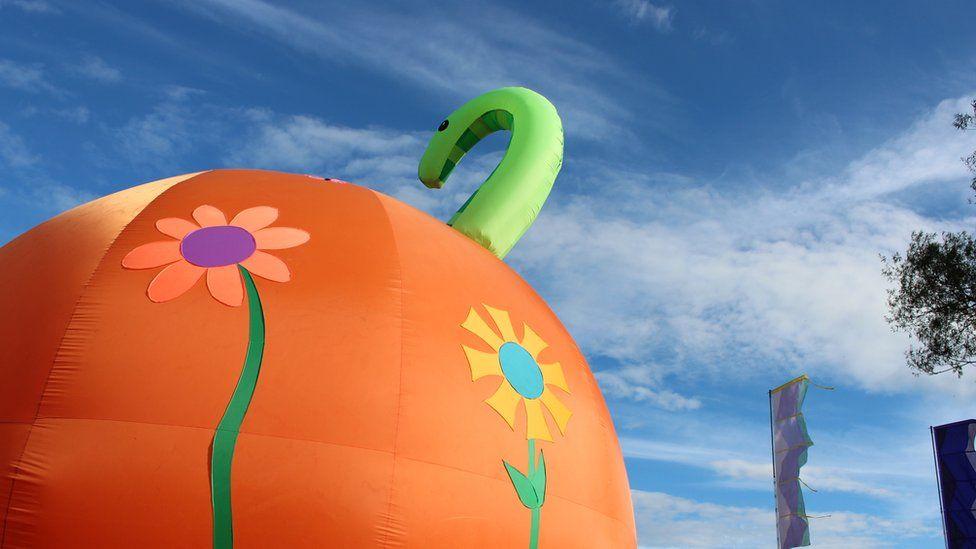 Mae'n ganmlwyddiant geni Roald Dahl eleni ac mae Gŵyl Llên Plant yr Eisteddfod yn dathlu gyda llond eirinen mawr wlanog o hwyl // To celebrate the 100th anniversary of Roald Dahl's birth, visitors to the Maes can explore inside this giant inflatable peach