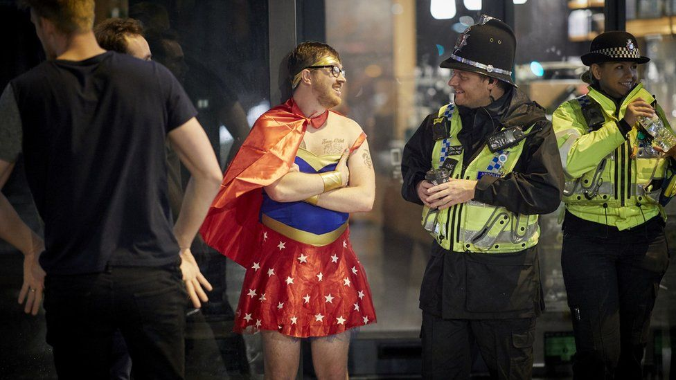 A man dressed as superwoman makes friendly conversation with a police officer