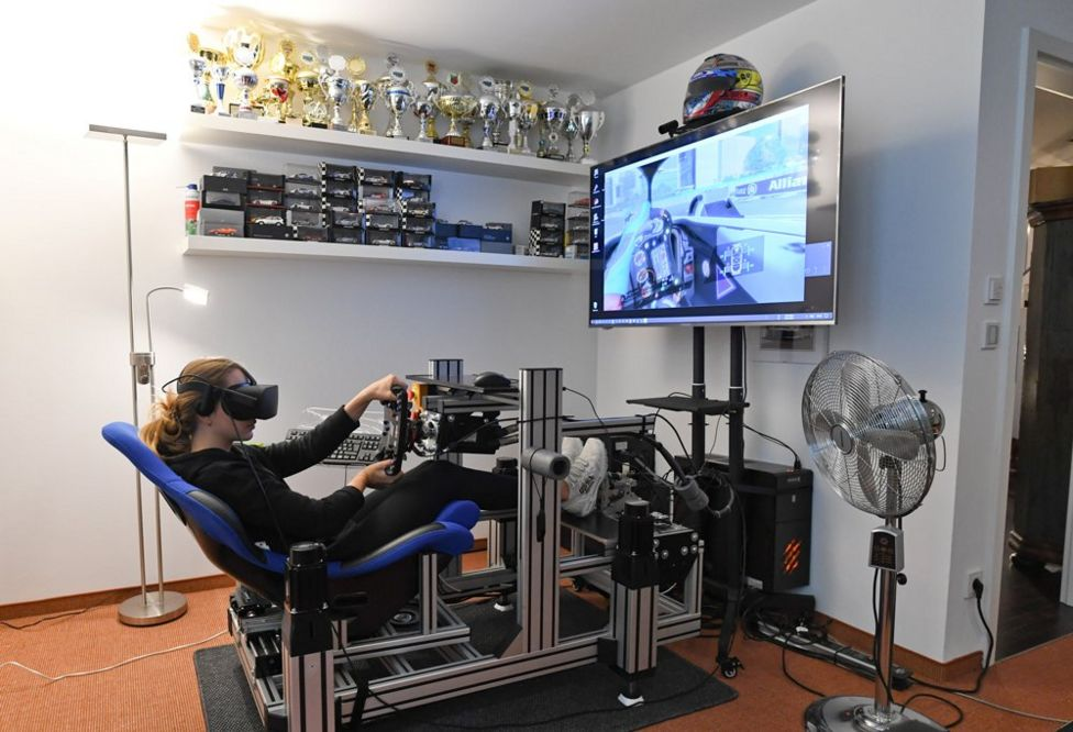 Formula 3 racer Sophia Floersch uses a virtual-reality simulator at home