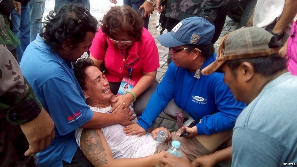 Rescuers comfort a survivor of the sinking (02 July 2015)
