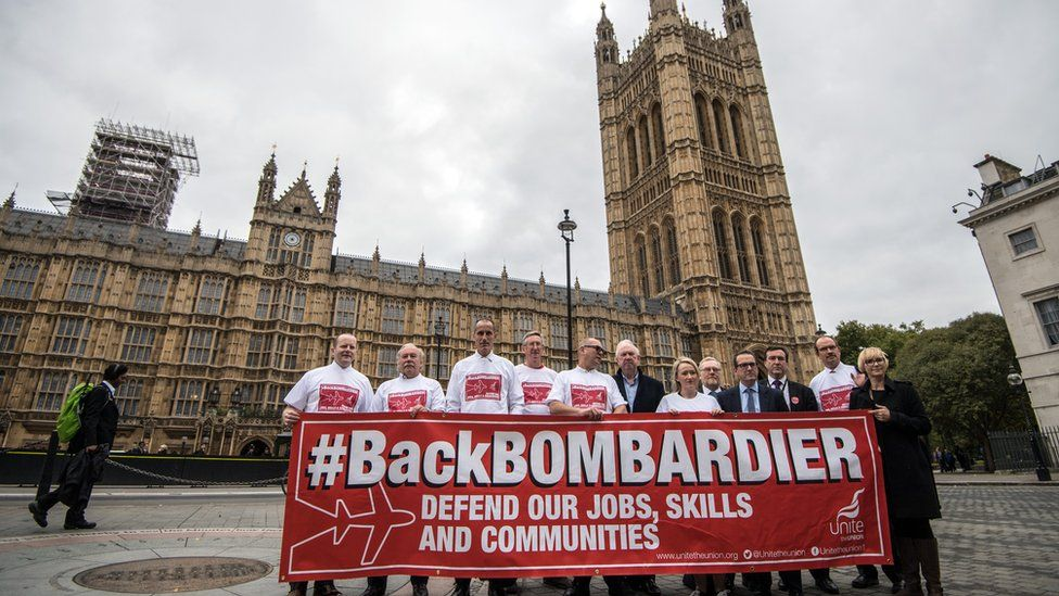 Workers from the Bombardier factory in Belfast hold a banner to highlight their situation