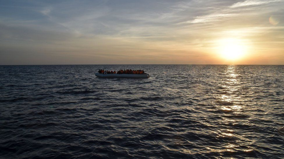 Migrants and refugees sit on a rubber boat before being rescued by the ship Topaz Responder run by Maltese NGO Moas and Italian Red Cross off the Libyan coast in the Mediterranean Sea, on November 5, 2016.