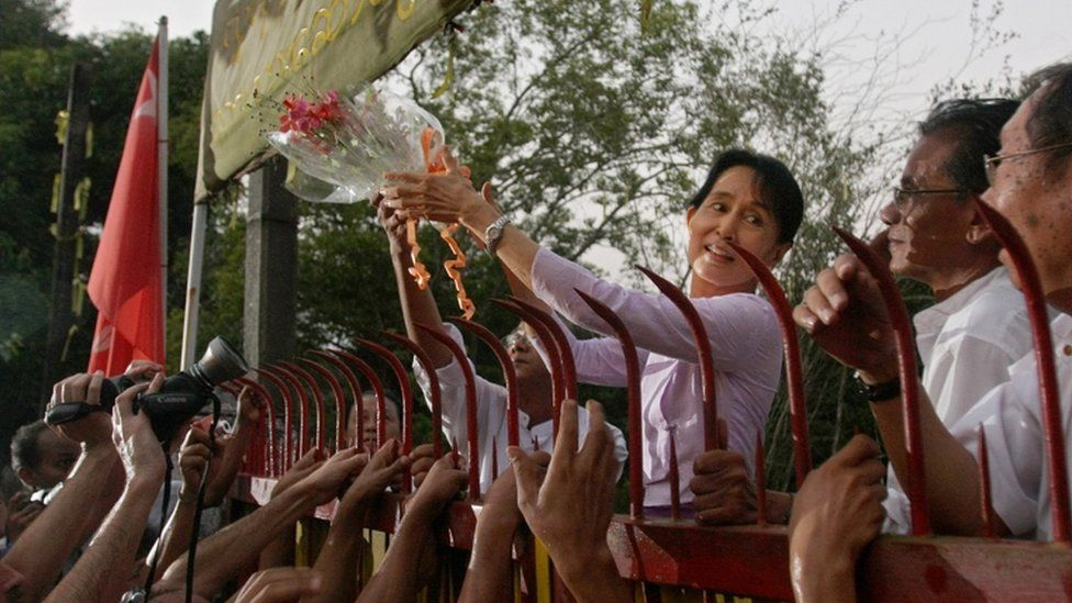 """Myanmar""""s detained opposition leader Aung San Suu Kyi holds a bouquet of flowers as she appears at the gate of her house after her release in Yangon on November 13, 2010. Myanmar""""s democracy leader Aung San Suu Kyi walked free from the lakeside home that has been her prison for most of the past two decades, to the delight of huge crowds of waiting supporters. Waving and smiling, the petite but indomitable Nobel Peace Prize winner appeared outside the crumbling mansion where she had been locked up by the military junta for 15 of the past 21 years."""