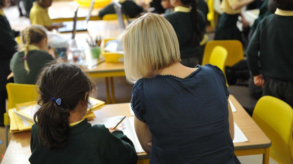 A female teacher helps a student