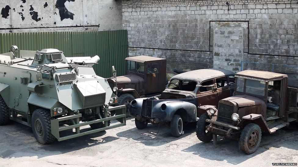 A British-made Saxon armoured personnel carrier standing next to classic cars which are yet to be restored