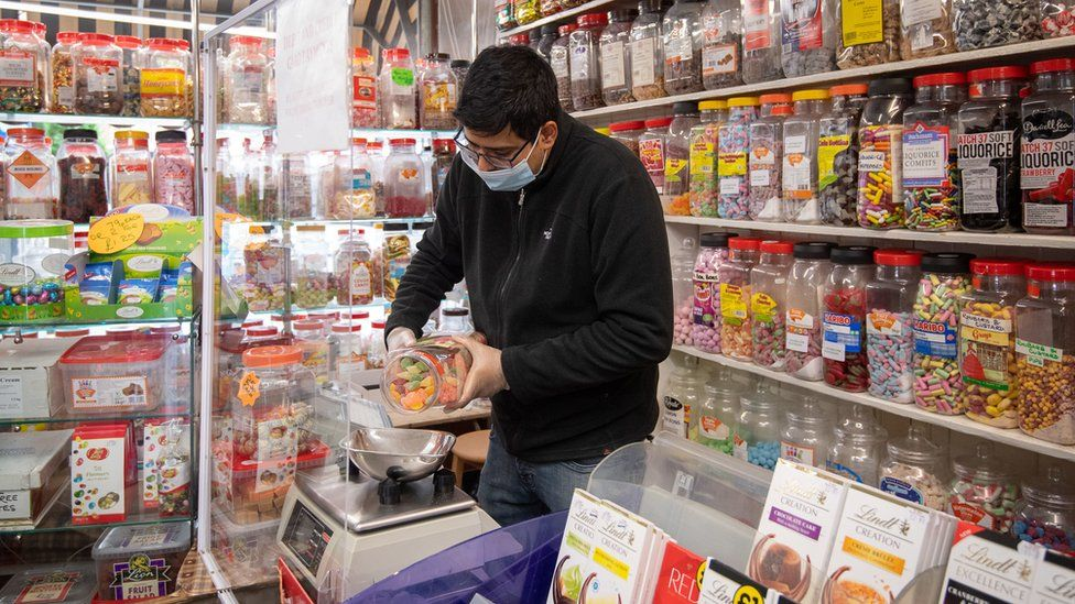 A man weighs out sweets in a sweet shop