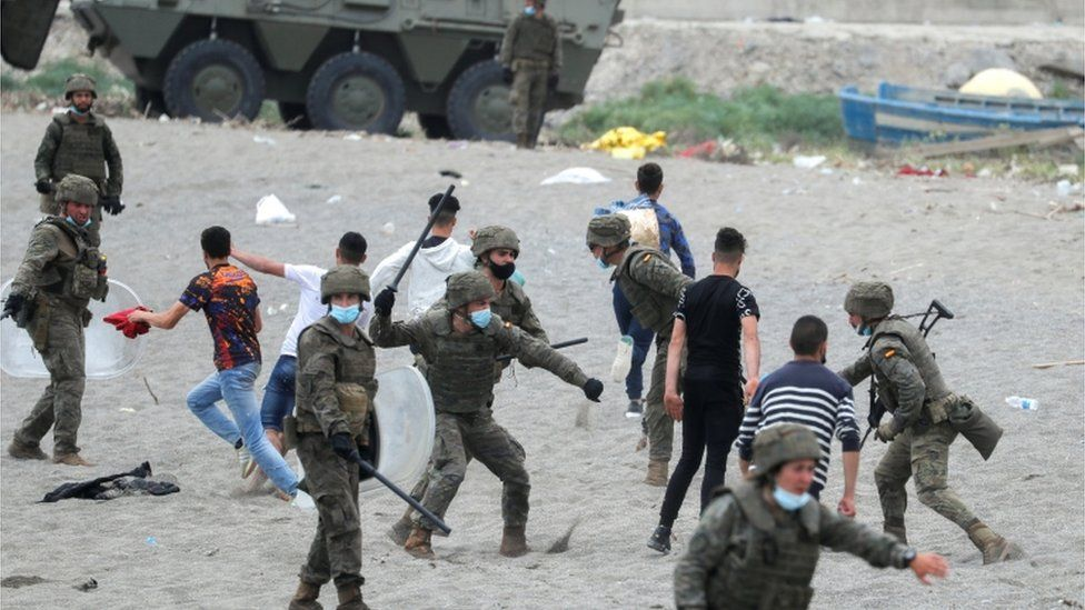 A Spanish soldier hits a Moroccan citizen at El Tarajal beach, near the fence between the Spanish-Moroccan border