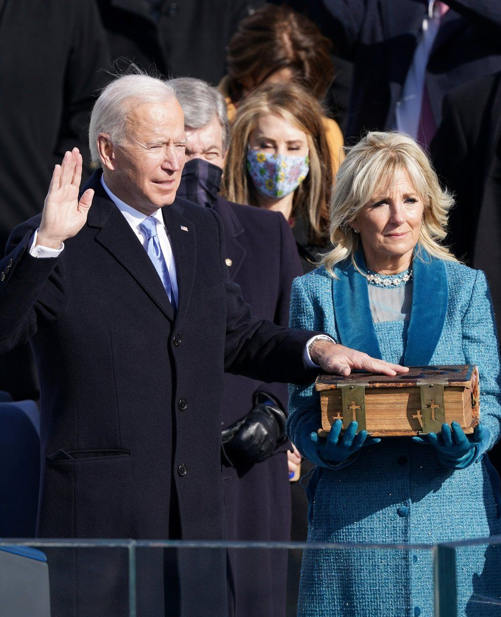 President Biden places his hand on a large Bible