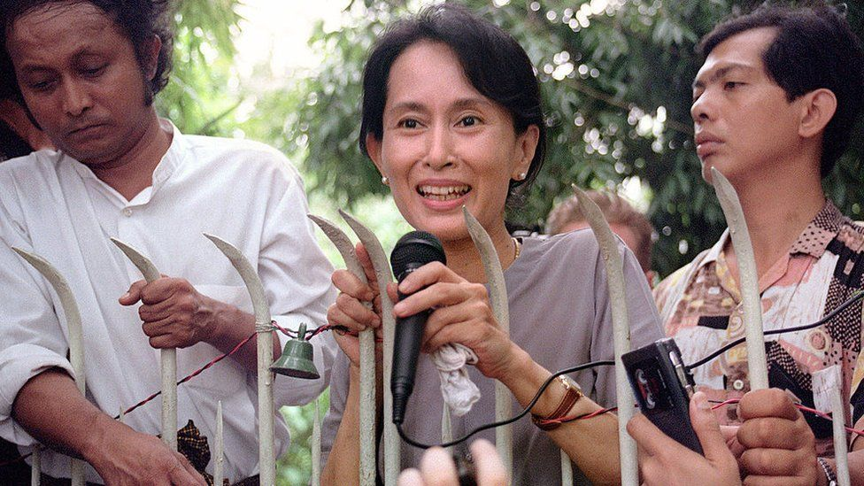 Myanmar pro-democracy leader and Nobel Peace laureate Aung San Suu Kyi (C) addresses 14 July 1995 hundreds of anxious Burmese supporters from the main gate of her family compound in Rangoon