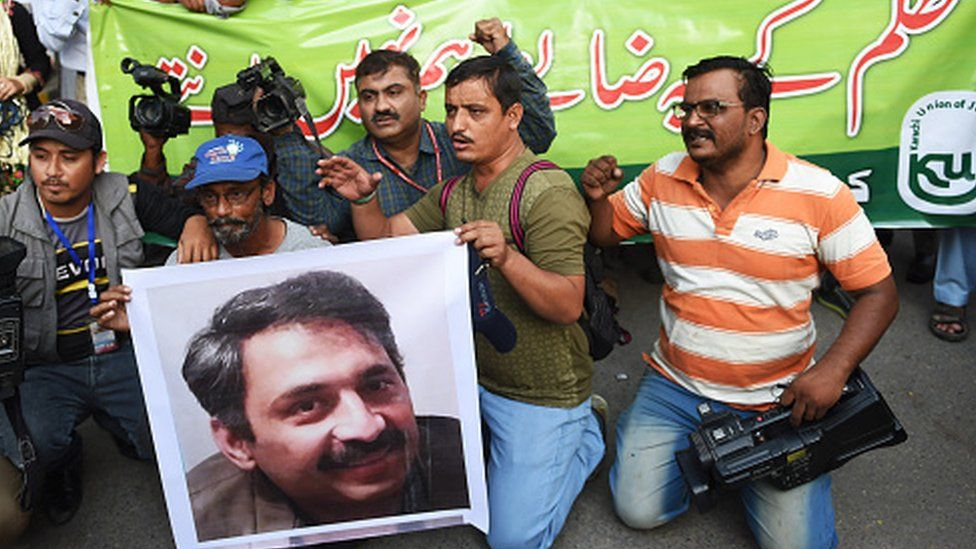 Pakistani journalists in Karachi hold a picture of Ahmed Noorani, a senior journalist of a local newspaper who was beaten by unknown attackers (30 October 2017)