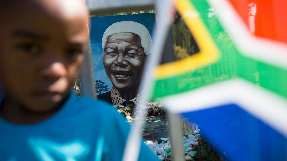 A boy plays with a South African national flag in front of a mural of Nelson Mandela in Soweto Township, as the funeral of former South African President takes place in Qunu, on December 15, 2013 in Soweto, South Africa