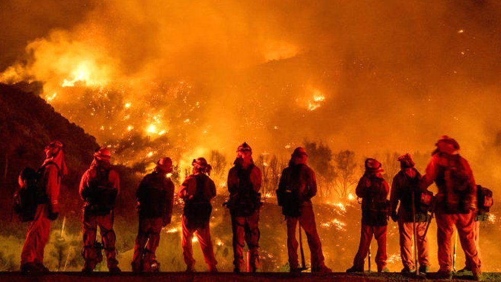 Firefighters watch as the El Dorado blaze burns a hillside near homes in Mountain Home Village, California, inside the San Bernardino National Forest, 9 September 2020