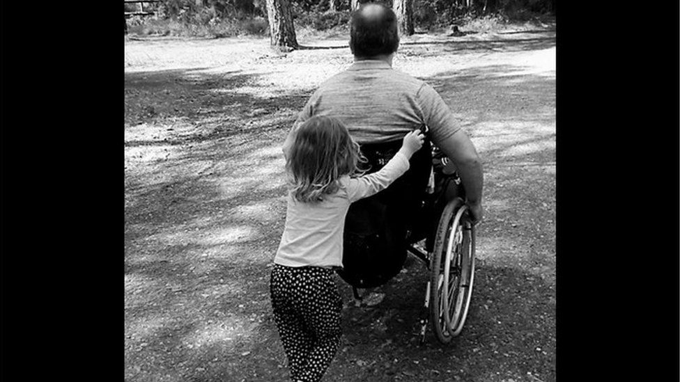 Ian Taverner with one of his daughters pushing him in a wheelchair